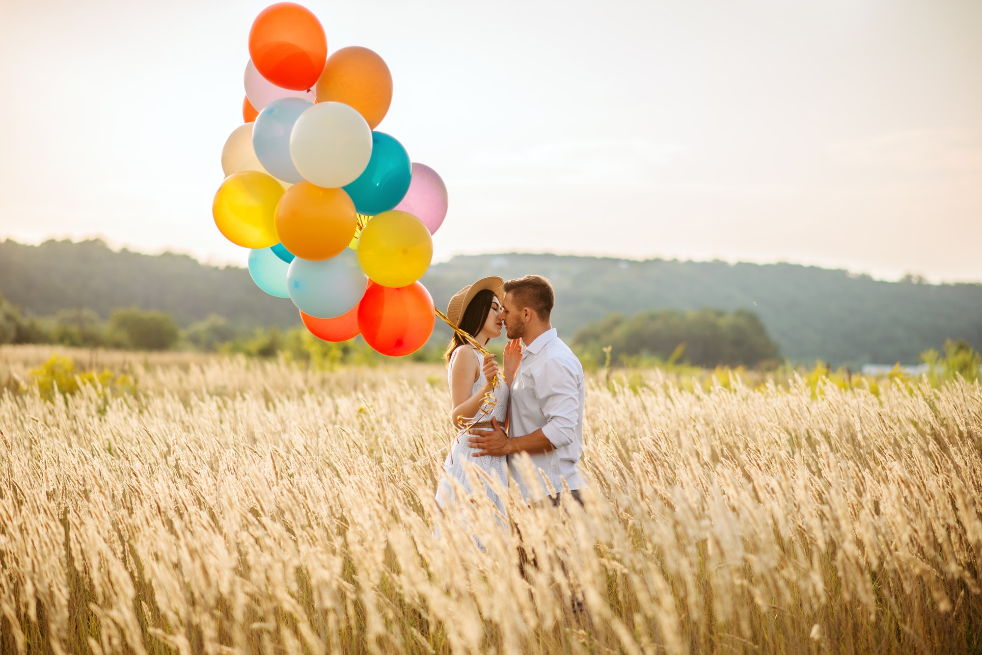 Love couple with balloons hugs in a rye field